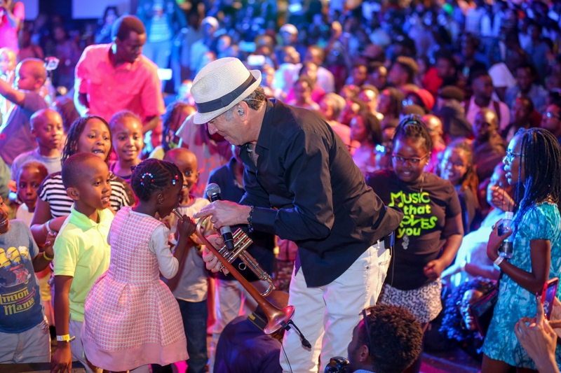 US based jazz star Ricky Braun enjoys blowing saxophone with a young jazz fan during the Safaricom International jazz festival.