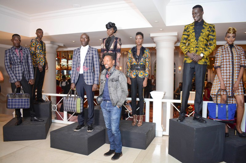 Fashion designer John Kaveke (front) models showcasing his designs.